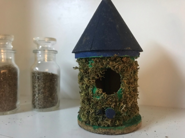 a small round wooded birdhouse covered in moss