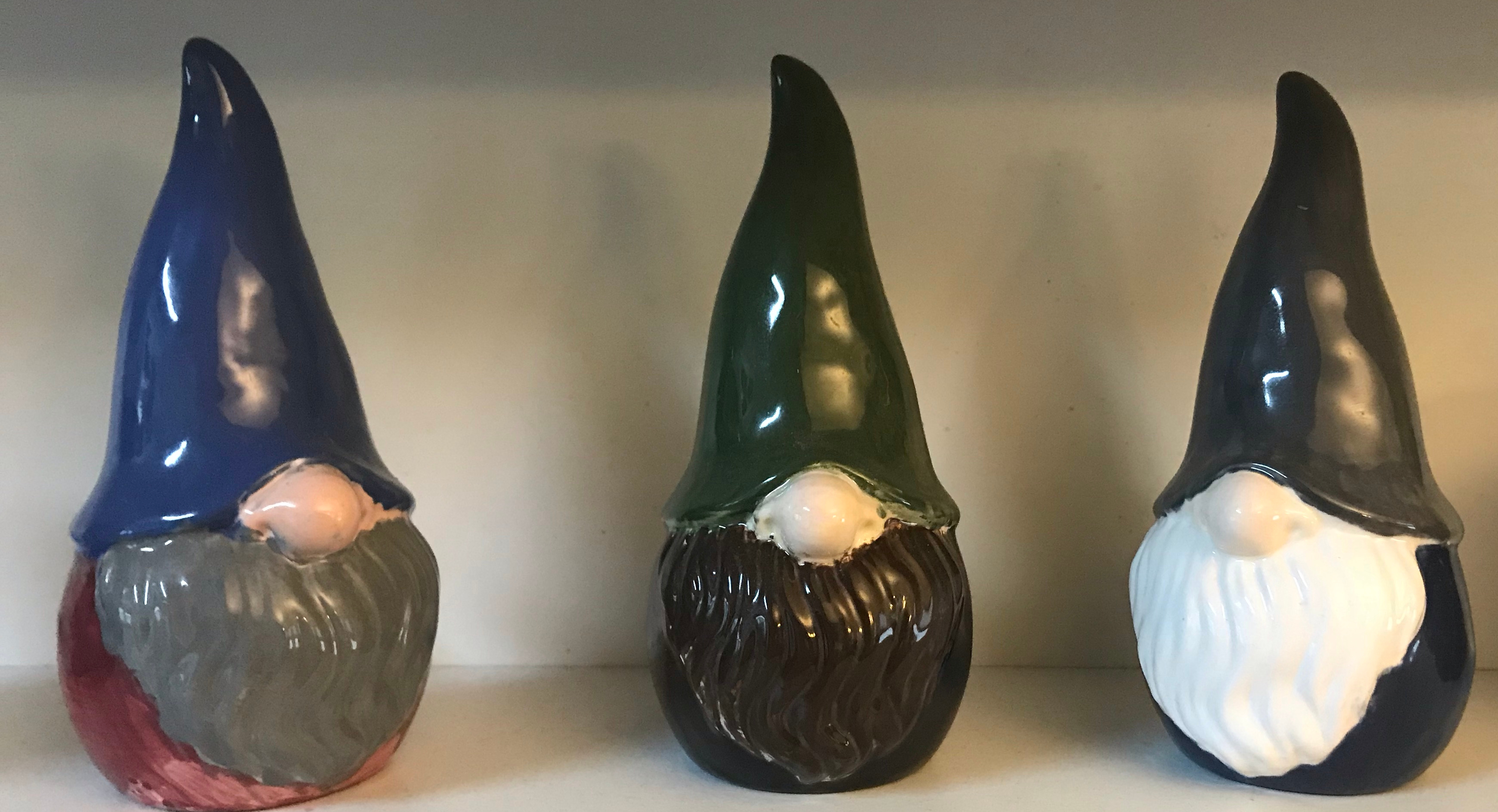 3 porcelain gnomes: one with a gray beard, red shirt, and blue hat, one with a brown beard, black shirt, and green hat, and one with a white beard, blue shirt, and gray hat