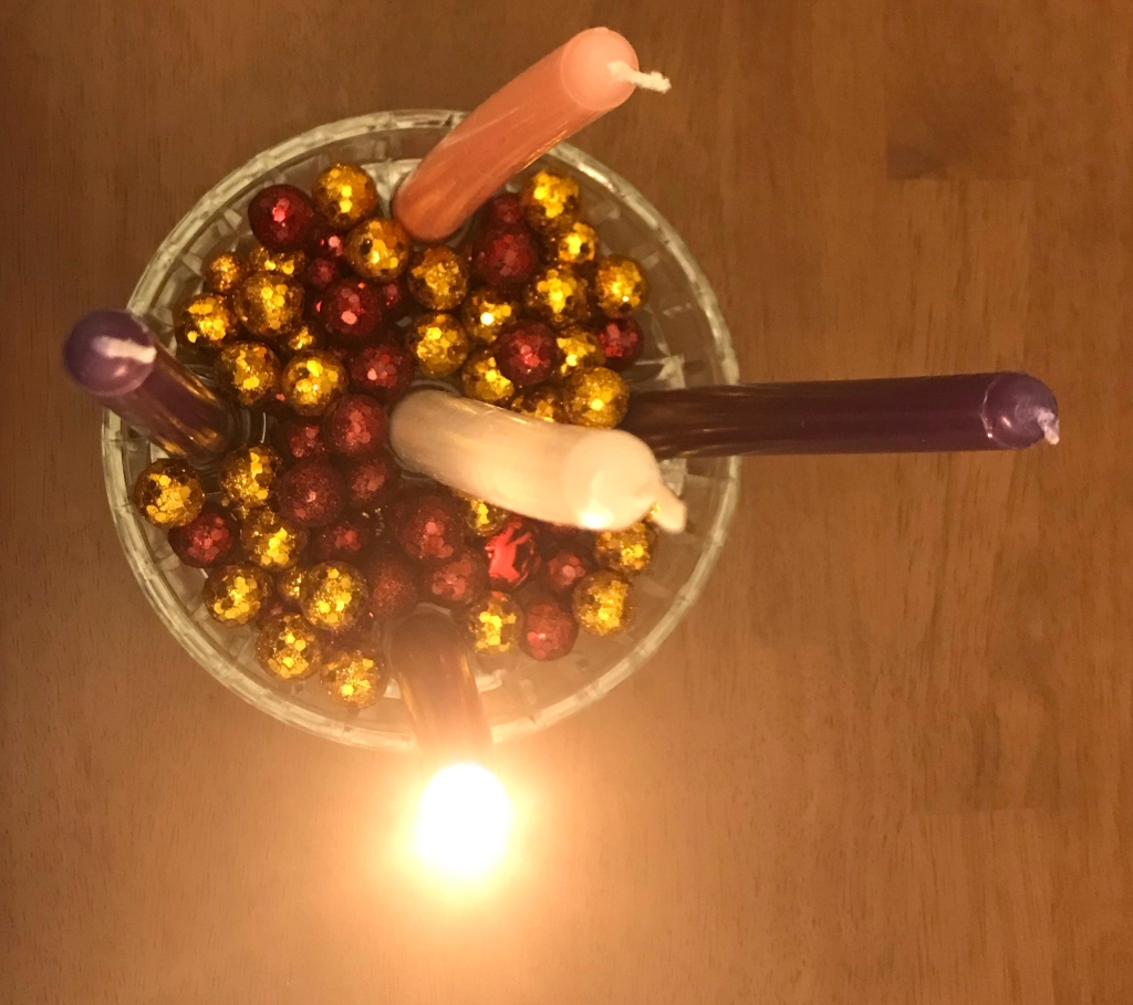 a pink, blue, and three purple taper candles in a glass bowl filled with red and gold Christmas baubles